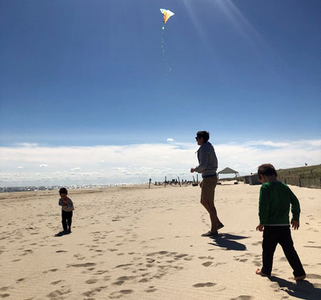 Kevin McKeown with his two boys flying a kite on beach
